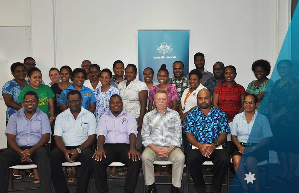 Peter Morris, the facilitator of the National Human Resource Development Plan 2020-2030 session, surrounded by the Australia Awards Vanuatu Alumni.